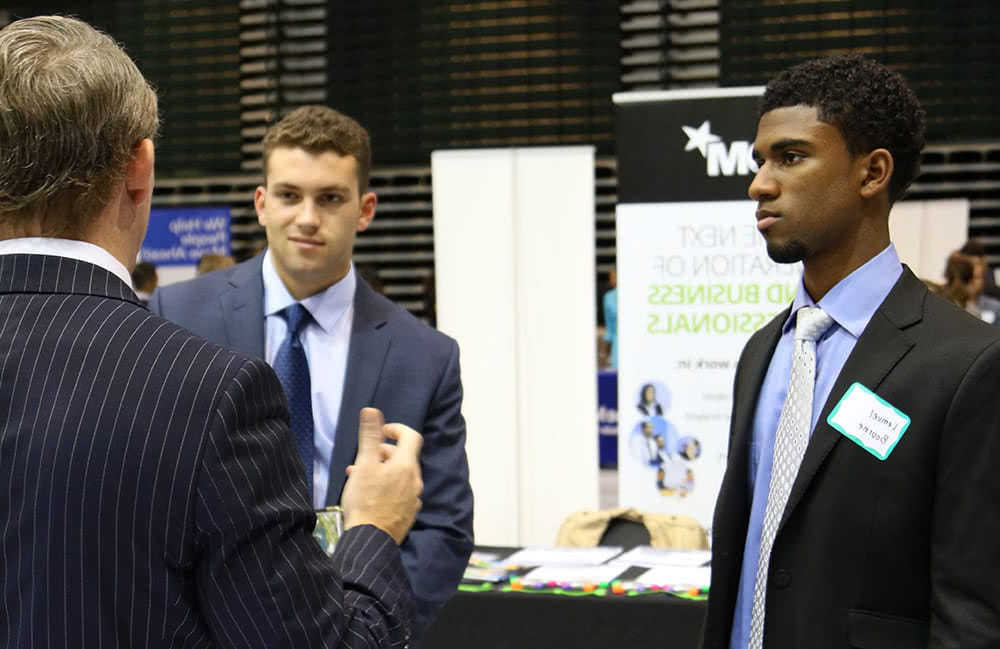 Two students wearing business suits talk to a recruiter at the career fair