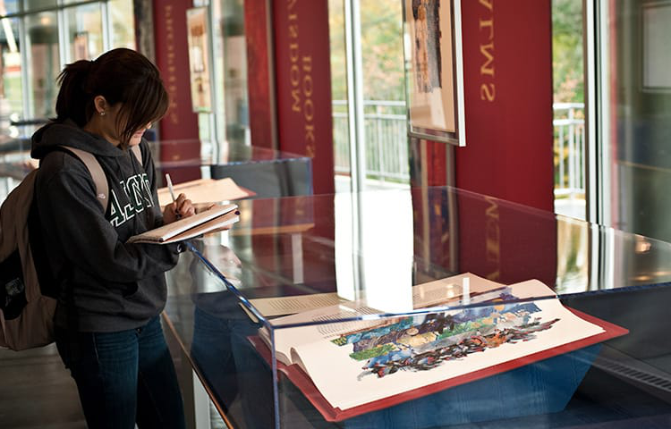 A female student taking notes in front of an exhibit with an illuminated manuscript