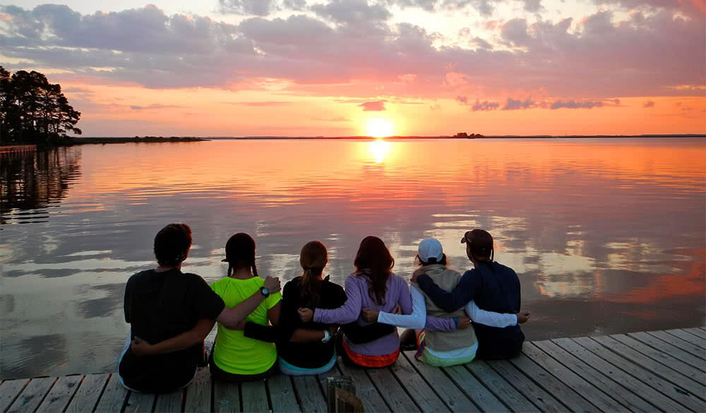 Students sitting on the edge of a pier with their arms around each other and looking out at a col要么ful sunset on the water