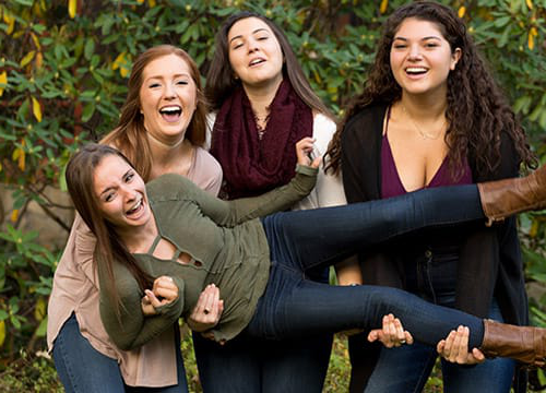 Three female students holding a fourth student, all smiling and laughing