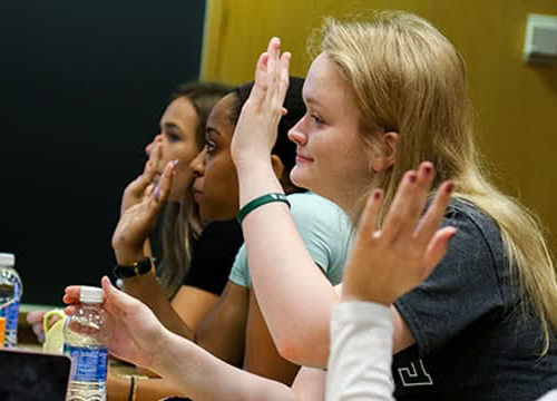 Students sitting in class and raising their hands to answer a question