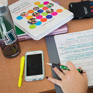 A student's hand resting next to a notebook, phone, textbook, and 葡京app water bottle