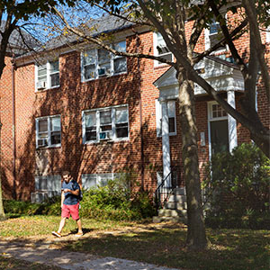 A student walking in front of a residence hall