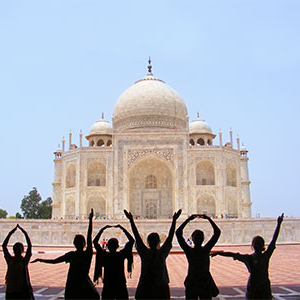 Students spelling out 葡京app with their hands in front of the Taj Mahal