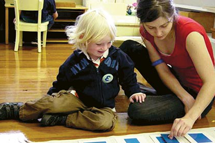A teacher doing hands-on learning with a young student